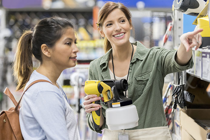 woman choosing a paint sprayer